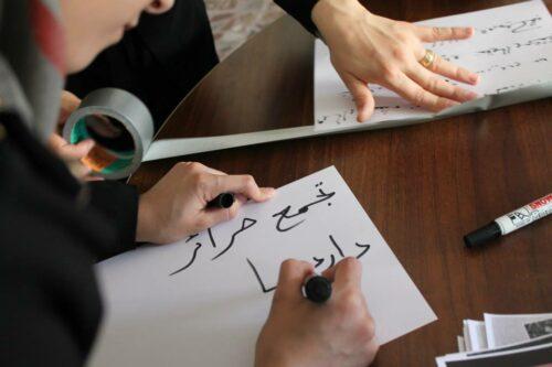 """Une femme inscrit sur une feuille les termes """"Rassemblement des femmes libres de Daraya"""". Page Facebook Tajammu' harâ'ir dârayâ"""